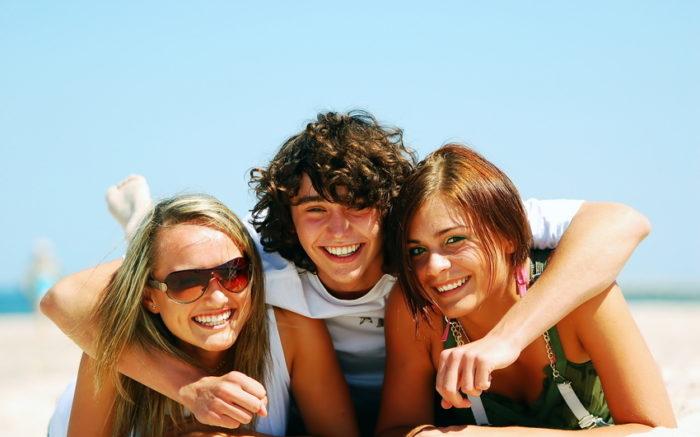 парень обнимает двух девушек
